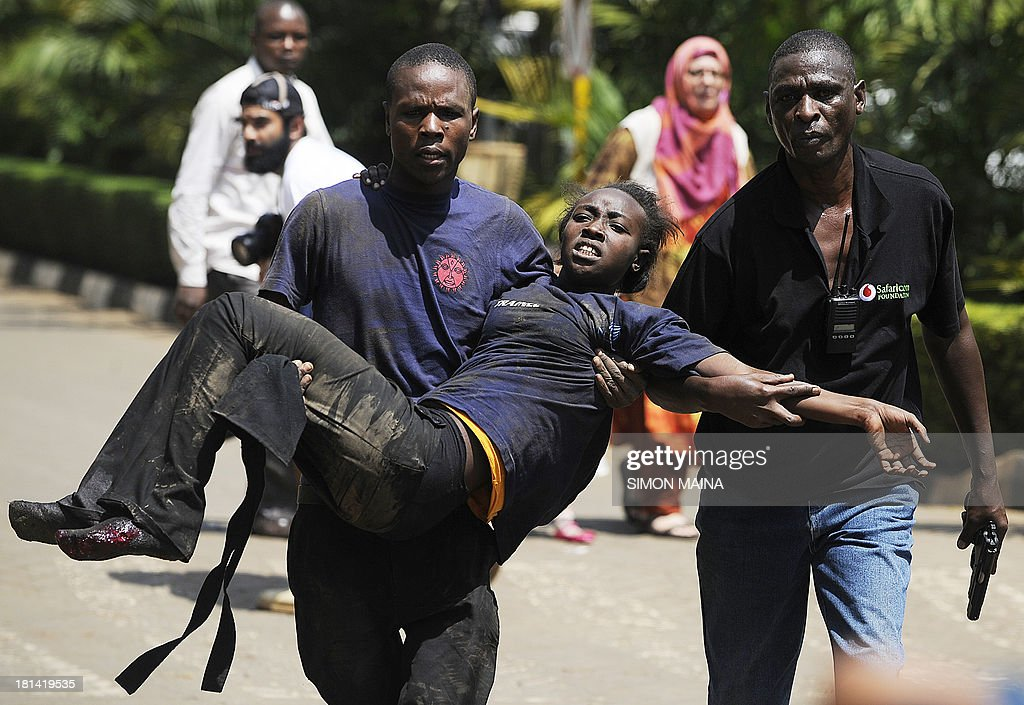 A Kenyan woman is helped to safety after masked gunmen stormed an upmarket mall and sprayed gunfire on shoppers and staff, killing at least six on September 21, 2013 in Nairobi. The Gunmen have taken at least seven hostages, police and security guards told an AFP reporter at the scene. AFP PHOTO/SIMON MAINA