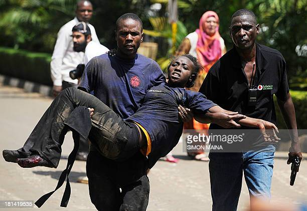 A Kenyan woman is helped to safety after masked gunmen stormed an upmarket mall and sprayed gunfire on shoppers and staff killing at least six on...