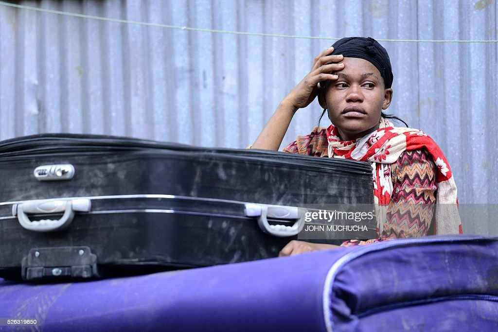 A Kenyan woman reacts as she looks at what used to be her home after a building collapsed in Nairobi on April 30, 2016. Torrential rainstorms in the Kenyan capital have left at least 14 people dead, police said, including at least seven crushed when a six-storey building collapsed, as rescue teams shifted rubble in a desperate search for survivors. / AFP / JOHN