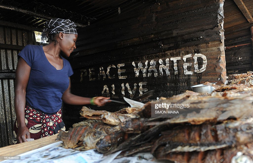 A Kenyan woman sells fish on the road side next to writing on an corrugated iron sheet house, urging for a peaceful poll on February,25,2013 in the sprawling Kibera slums. Kenya is gearing up for presidential, gubernatorial, senatorial elections on March 4, the first since bloody post-poll violence five years ago in which more than 1,100 people died after contested results. AFP PHOTO/SIMON MAINA