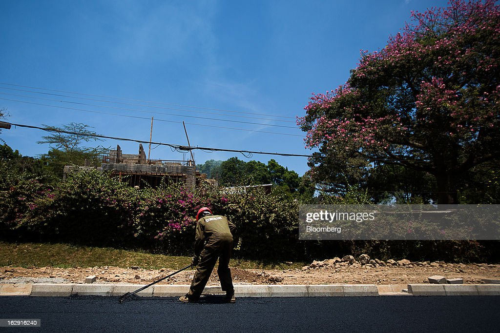 A Kenyan worker rakes asphalt as he lays a new road in Nairobi, Kenya, on Friday, March 1, 2013. Next week's presidential vote will be the first since disputed elections in 2007 triggered ethnic fighting in which more than 1,100 people died and another 350,000 fled their homes. Photographer: Trevor Snapp/Bloomberg via Getty Images