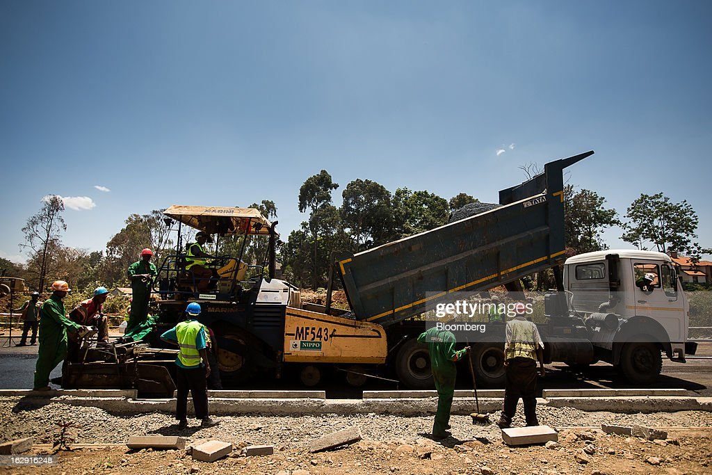 Kenyan workers lay asphalt on a new road in Nairobi, Kenya, on Friday, March 1, 2013. Next week's presidential vote will be the first since disputed elections in 2007 triggered ethnic fighting in which more than 1,100 people died and another 350,000 fled their homes. Photographer: Trevor Snapp/Bloomberg via Getty Images