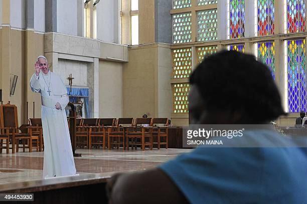 Kenyans attend a lunch time prayer mass with a cardboard cutout of Pope Francis at the Holy Family Basilica on October 27 2015 in Nairobi Pope...