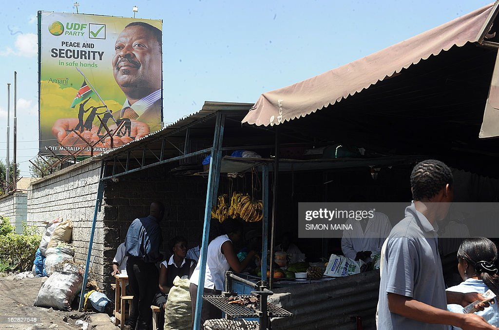 Kenyans have lunch on February 28, 2013 in front of an election campaign billboard for presidential candidate and leader of the United Democratic Forum (UDF), Musalia Mudavadi, in Nairobi. Kenya is gearing up for general elections on March 4, the first since bloody post-poll violence five years ago in which more than 1,100 people died after contested results.