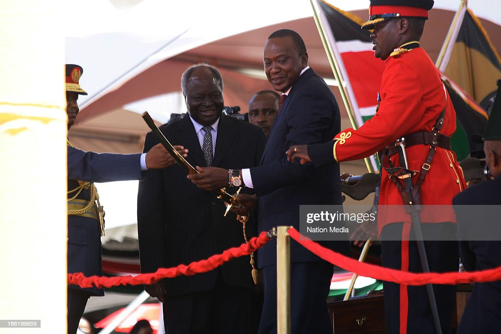 Kenya's 4th President Uhuru Kenyatta hands a ceremonial sword to his aide de-camp after it was handed to him by President Mwai Kibaki and General Julius Karangi, Chief of Staff, on April 9, 2013 in Nairobi, Kenya. Kenyatta received masses of support from the citizens of Kenya despite being under investigation for crimes against humanity.