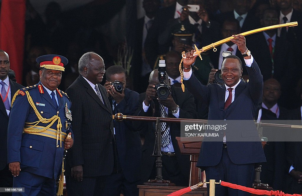 Kenya's 4th President Uhuru Kenyatta receives a symbolic sword of power from outgoing president Mwai Kibaki (2L) after he was sworn into office on April 9, 2013 in Nairobi. Uhuru Kenyatta was sworn in as Kenya's fourth president on Tuesday to thunderous cheers from tens of thousands of supporters, despite facing trial on charges of crimes against humanity. AFP PHOTO / TONY KARUMBA