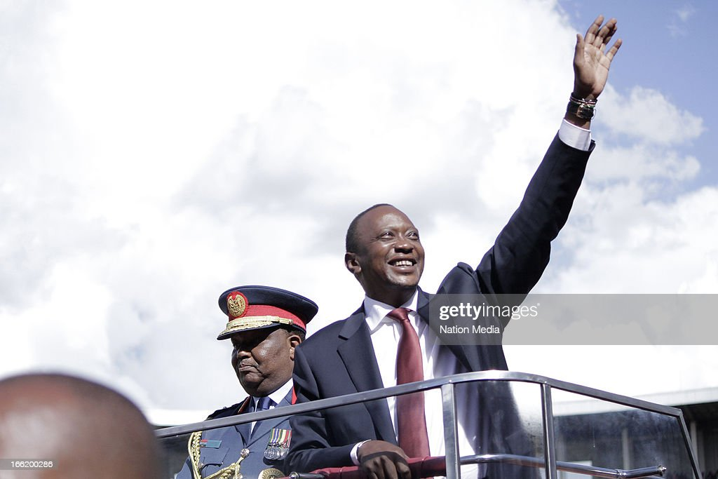 Kenya's 4th President Uhuru Kenyatta waves at the crowd on April 9, 2013 in Nairobi, Kenya. With him is General Julius Karangi, Kenya Defence Forces Chief of Staff. Kenyatta received masses of support from the citizens of Kenya despite being under investigation for crimes against humanity.