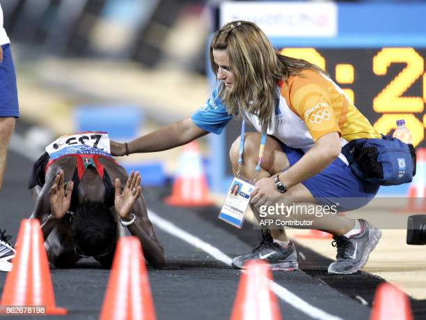 Kenya's Catherine Ndereba the 2003 world champion bowing down on the track exhausted is helped by a track official after the Kenyan came in second in...