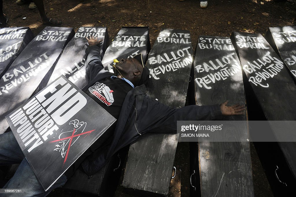 A Kenya's civil activist, lying on a bed, holds a sign during a demonstration in Nairobi, on January 16, 2013, during a 'State Burial' for the members of Kenyan parliament proposal to award themselves millions of shillings in a selfish send-off deal that included state funerals. Kenya's president rejected plans by members of parliament to triple their end-of-term bonuses and award themselves diplomatic passports, bodyguards for life and state funerals. In their last act before parliament closed for March 4 elections, Kenyan lawmakers, already among the best paid in the world, tried for a second time in a few months to increase their end-term bonus to 9.3 million shillings ($107,200) each.
