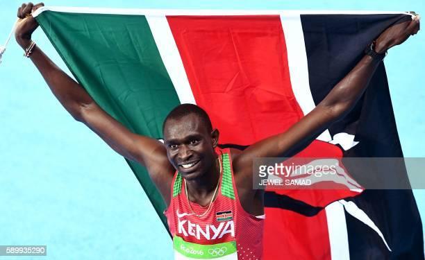 TOPSHOT Kenya's David Lekuta Rudisha waves his national flag as he celebrates winning the Men's 800m Final during the athletics event at the Rio 2016...