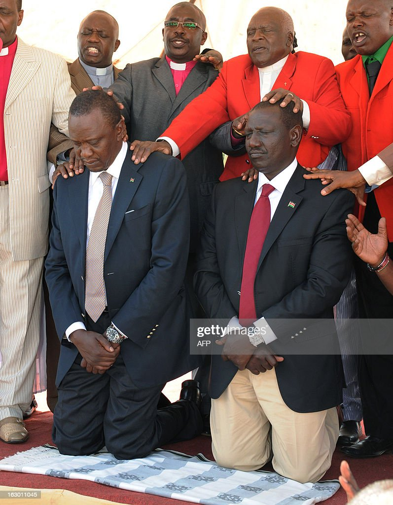 Kenya's Deputy Prime Minister and The National Alliance (TNA) presidential candidate Uhuru Kenyatta (bottom-L) kneels next to his running mate William Ruto as they are prayed for on March 3, 2013 during an interdenominational prayer in Kiambu, 48 hours ahead of presidential, gubernatorial and senatorial elections. Kenyans prayed for peace on the eve of the first elections since bloody post-poll unrest shook the nation five years ago, with a top presidential candidate facing a crimes against humanity trial over the violence.