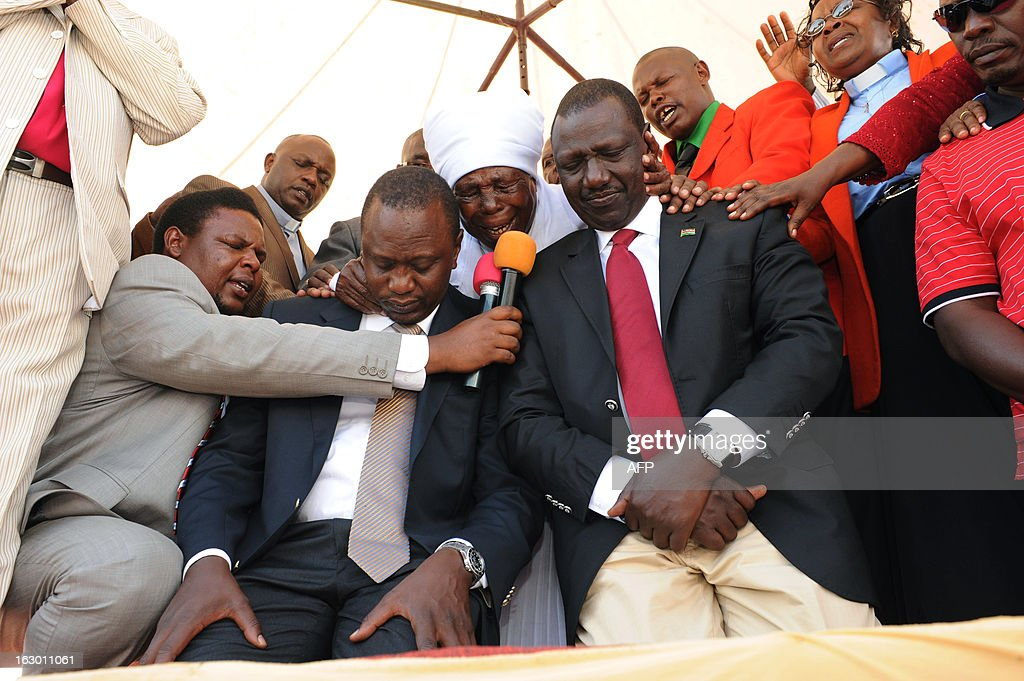 Kenya's Deputy Prime Minister and The National Alliance (TNA) presidential candidate Uhuru Kenyatta (2nd L) kneels next to his running mate William Ruto as they are prayed for on March 3, 2013 during an interdenominational prayer in Kiambu, 48 hours ahead of presidential, gubernatorial and senatorial elections. Kenyans prayed for peace on the eve of the first elections since bloody post-poll unrest shook the nation five years ago, with a top presidential candidate facing a crimes against humanity trial over the violence.