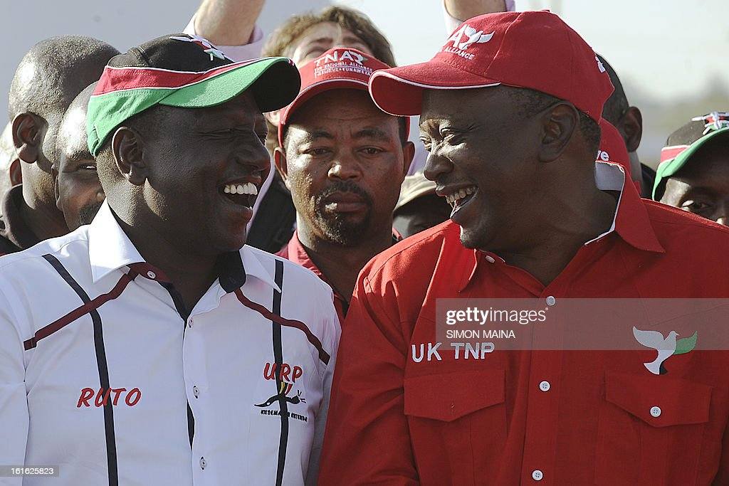 Kenya's Deputy Prime Minister Uhuru Kenyatta (R), who is also the Jubilee Alliance Presidential candidate, speaks with his running mate William Ruto on February 13 ,2013 before addresses supporters during a political rally in the capital Nairobi, ahead of next month's general election.