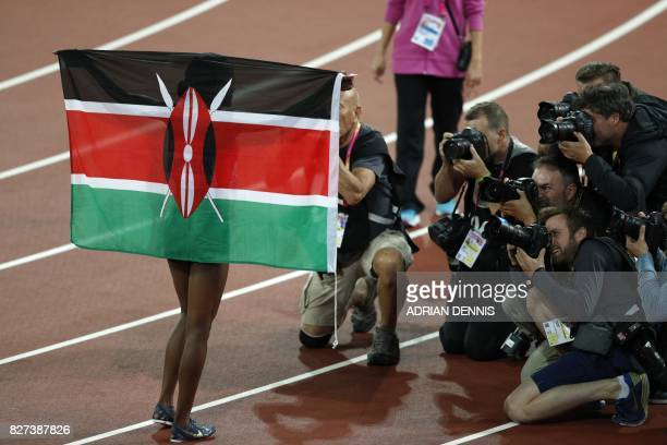 Kenya's Faith Chepngetich Kipyegon celebrates with the Kenyan flag after winning the final of the women's 1500m athletics event at the 2017 IAAF...