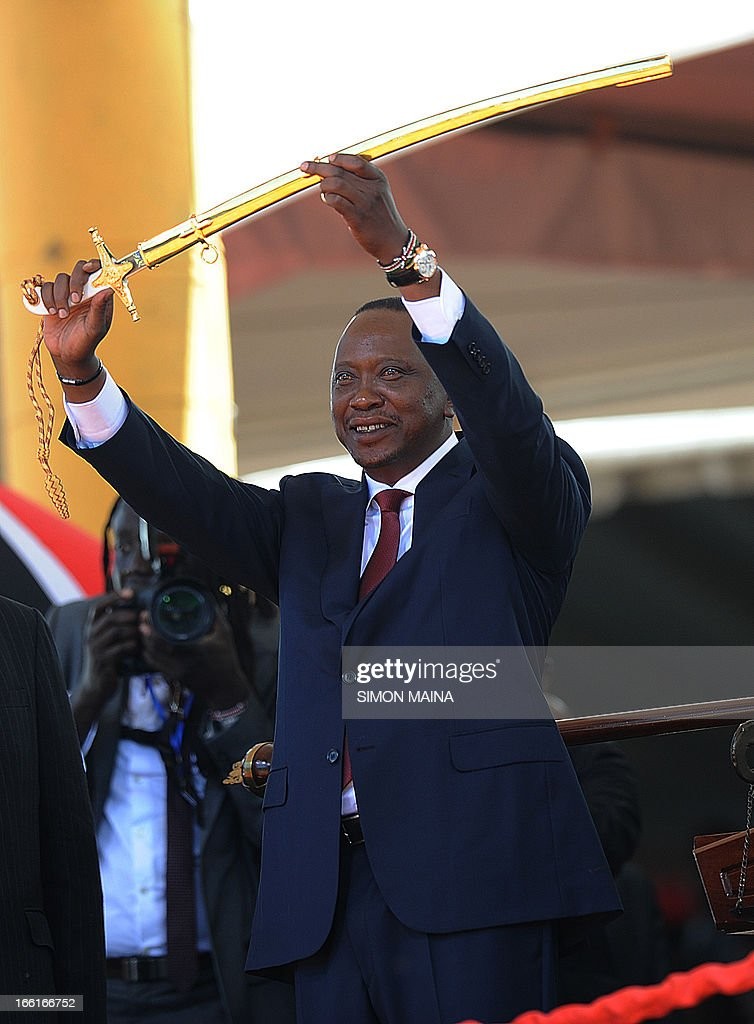 Kenya's fourth president Uhuru Kenyatta lifts a sword as a symbol of authority during his inauguration at the Moi International Sports Center Kasarani in Nairobi on April 9, 2013. Uhuru Kenyatta was sworn in as Kenya's fourth president on Tuesday to thunderous cheers from tens of thousands of supporters, despite facing trial on charges of crimes against humanity.