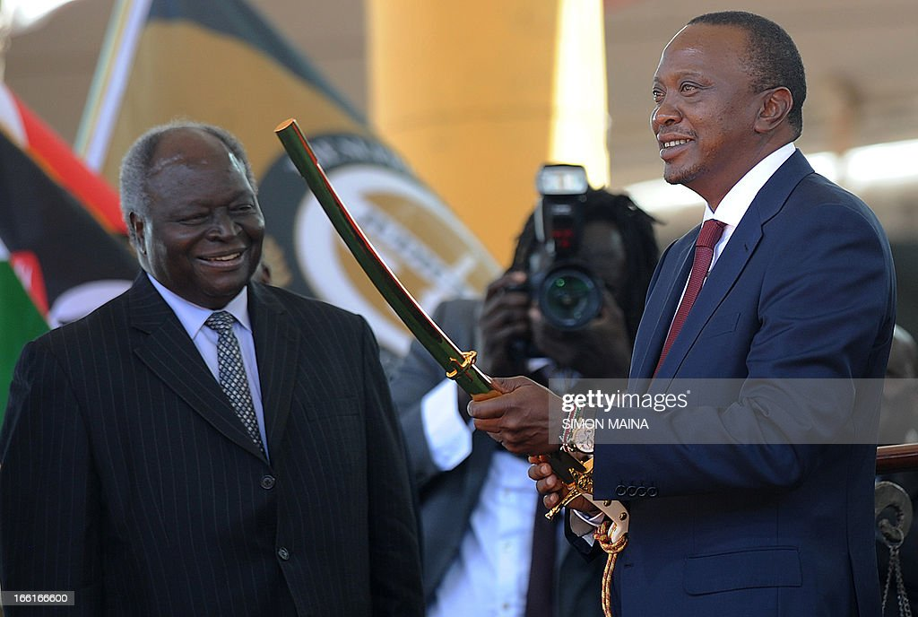 Kenya's fourth president Uhuru Kenyatta receives a sword as a symbol of authority from former president Mwai Kibaki (L) during his inauguration at the Moi International Sports Center Kasarani in Nairobi on April 9, 2013. Uhuru Kenyatta was sworn in as Kenya's fourth president on Tuesday to thunderous cheers from tens of thousands of supporters, despite facing trial on charges of crimes against humanity.
