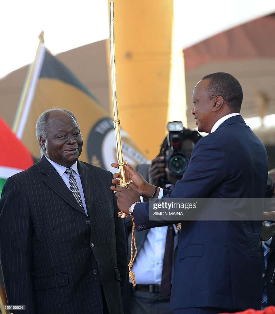 Kenya's fourth president Uhuru Kenyatta receives a sword as a symbol of authority from former president Mwai Kibaki (L) during his inauguration at the Moi International Sports Center Kasarani in Nairobi on April 9, 2013. Uhuru Kenyatta was sworn in as Kenya's fourth president on Tuesday to thunderous cheers from tens of thousands of supporters, despite facing trial on charges of crimes against humanity. AFP PHOTO/SIMON MAINA