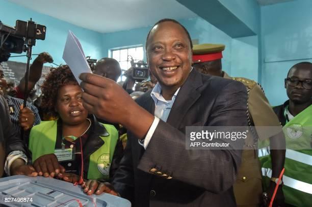 Kenya's incumbent President Uhuru Kenyatta holds a ballot paper at the polling station during the August 8 2017 presidential election in Gatundu...