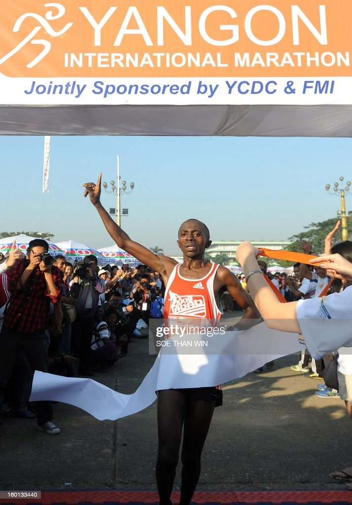 Kenya's Kariuki Gitau, 25, celebrates as he crosses the finish line to win Myanmar's first international marathon in decades in Yangon on January 27, 2013. Hundreds of runners streamed through Yangon on January 27 for Myanmar's first international marathon in decades, in another sign of the dramatic changes sweeping the former army-ruled country. AFP PHOTO/Soe Than WIN