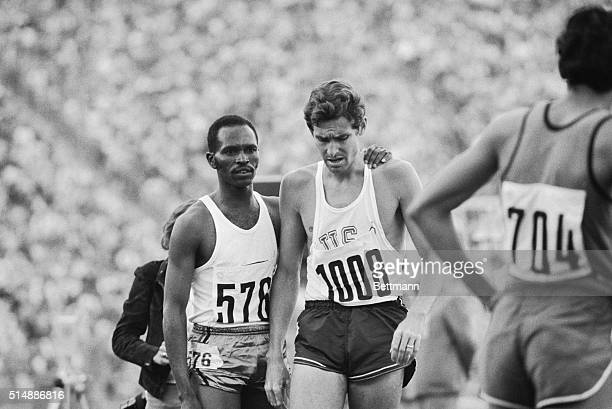 Kenya's Kipchoge Keino winner of the fourth heat of the 1500 meter Olympic race for men comforts his longtime foe Jim Ryun of the US after Ryun took...