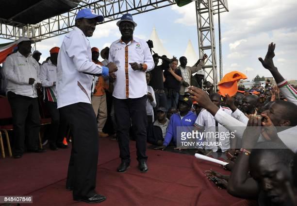 Kenya's main political opposition National Super Alliance presidential flagbearer Raila Odinga gestures next to his running mate Kalonzo Musyoka...