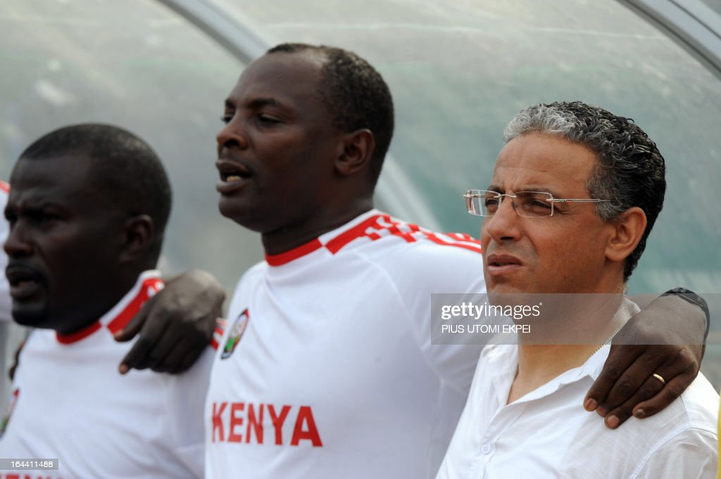 Kenya's national football team's Algerian coach Adel Amrouche (R) stands with members of the technical crew during as they sing Kenya's national anthem before the FIFA 2014 World Cup qualifying match against Nigeria on March 23, 2013 in Calabar. The match ended in a 1 - 1 draw.
