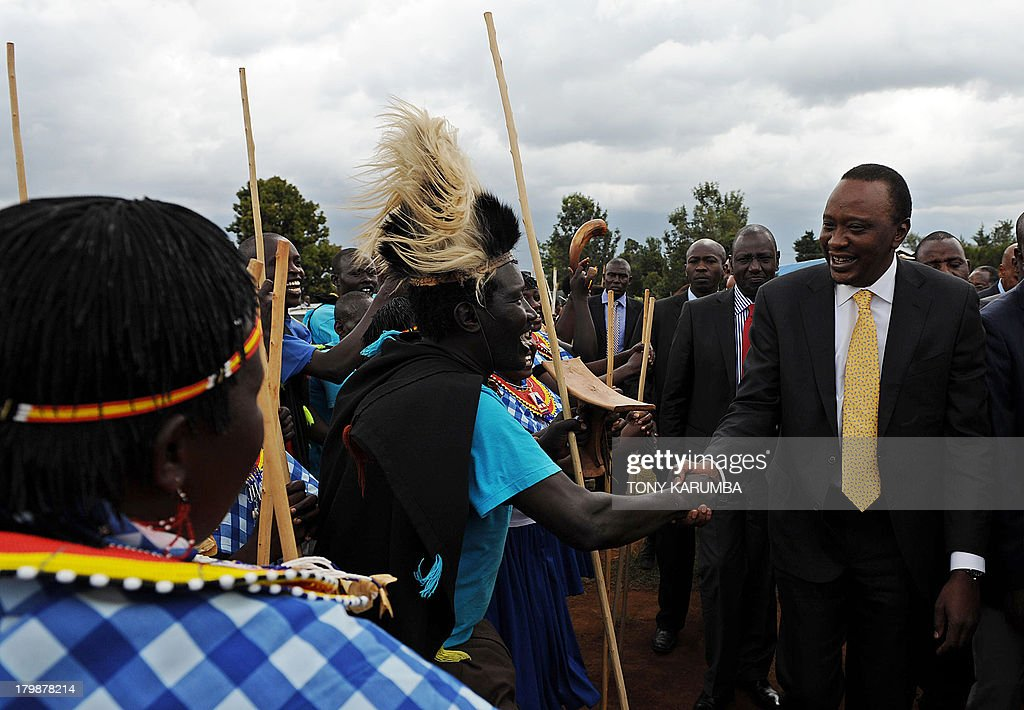 Kenya's President, Uhuru Kenyatta (R), accompanied by his deputy, William Ruto (2nd R) are welcomed by a dancing troupe on September 7, 2013 at Eldoret in Kenya's North-Rift, where the leaders distributed over 90 million Kenya shillings (over 1 million US dollars) to some of the last remaining internally displaced persons (IDP) in the rift for resettlement. Over 200 families of IDPs benefited from the government's drive to re-settle the remaining IDPs in fulfilment of its campaign promise to resolve the displaced and disenfranchised (squatters) problems during its rule.