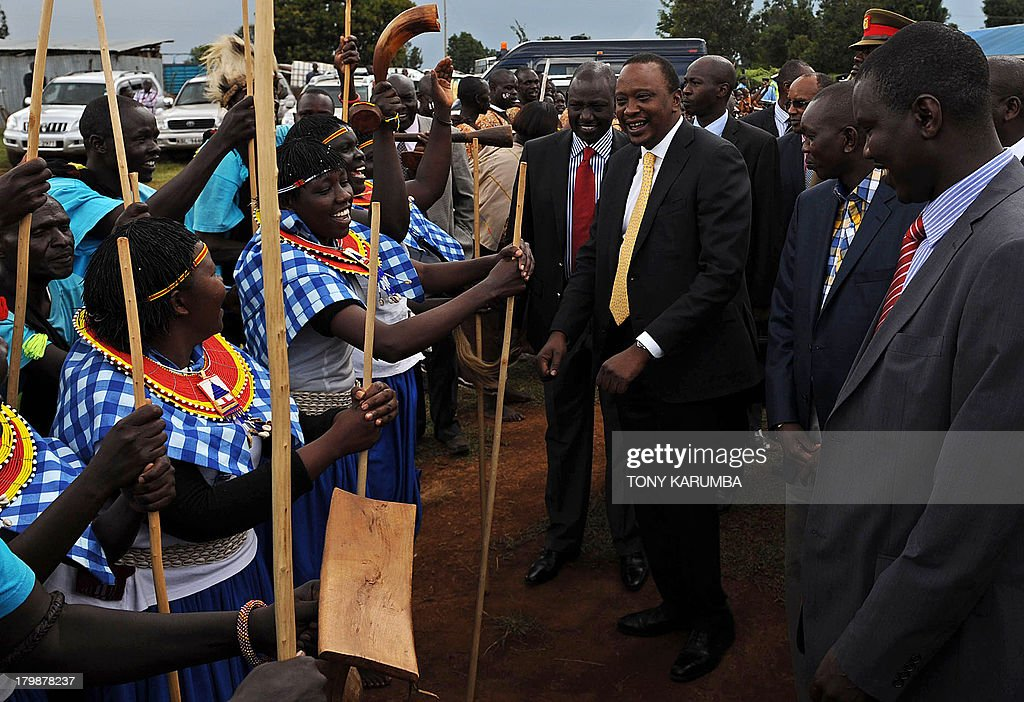Kenya's President, Uhuru Kenyatta (C), accompanied by his deputy, William Ruto (C,L) are welcomed by a dancing troupe on September 7, 2013 at Eldoret in Kenya's North-Rift, where the leaders distributed over 90 million Kenya shillings (over 1 million US dollars) to some of the last remaining internally displaced persons (IDP) in the rift for resettlement. Over 200 families of IDPs benefited from the government's drive to re-settle the remaining IDPs in fulfilment of its campaign promise to resolve the displaced and disenfranchised (squatters) problems during its rule.