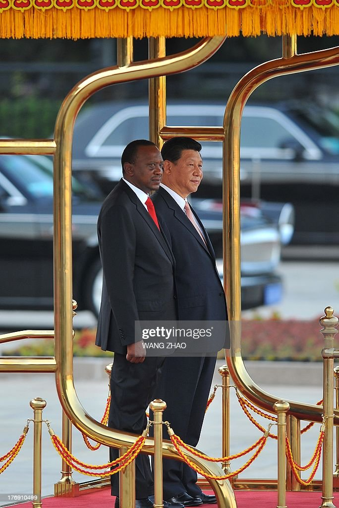 Kenya's President Uhuru Kenyatta (L) and Chinese President Xi Jinping (R) prepare to inspect Chinese honour guards during a welcoming ceremony outside the Great Hall of the People in Beijing on August 19,2013. Uhuru Kenyatta is on a visit to China from August 18 to 23.