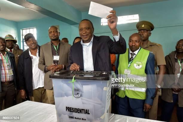 Kenya's President Uhuru Kenyatta casts his ballot as he votes at a polling station at Mutomo primary school in Kiambu on October 26 2017 as polls...