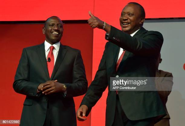 Kenya's President Uhuru Kenyatta flanked by deputy president William Ruto gestures during the unveiling of the Jubilee Party's manifesto on June 26...