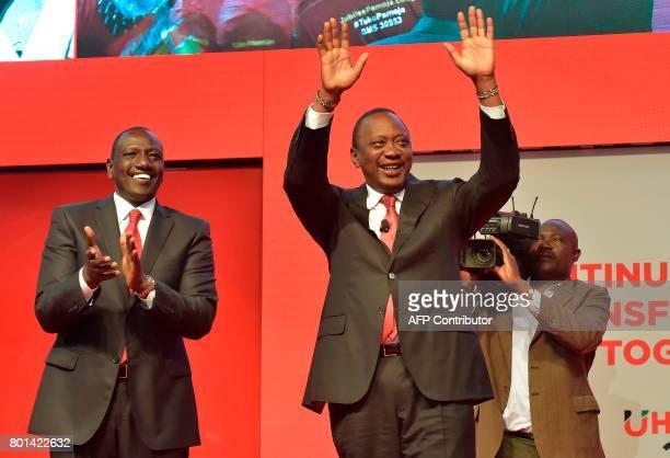 Kenya's President Uhuru Kenyatta flanked by deputy president William Ruto reacts during the unveiling of the Jubilee Party's manifesto on June 26...
