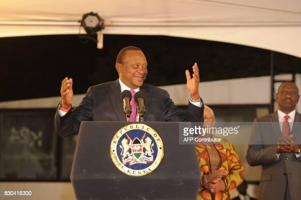 Kenya's President Uhuru Kenyatta flanked by his wife Margaret Gakuo Kenyatta gestures while speaking following the Electoral Commission's official...
