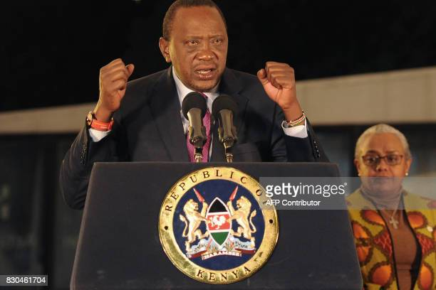 Kenya's President Uhuru Kenyatta flanked by his wife Margaret Gakuo Kenyatta speaks following the Electoral Commission's official announcement of the...