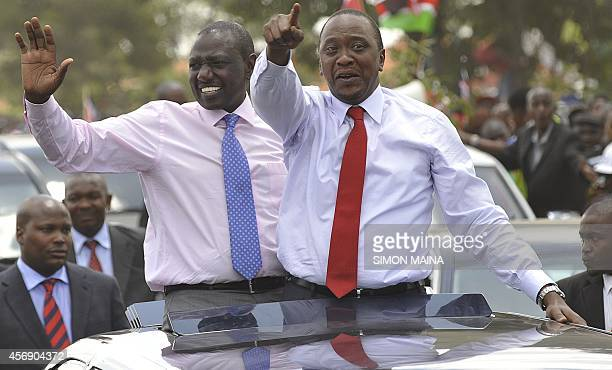 Kenya's president Uhuru Kenyatta waves to the welcoming crowd flanked by deputypresident William Ruto on October 9 2014 in Nairobi a day after...