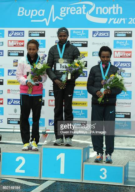 Kenya's Priscah Jeptoo celebrates winning the Women's Elite race of the 2013 Great North Run ahead of Ethiopia's Meseret Defar who came second and...