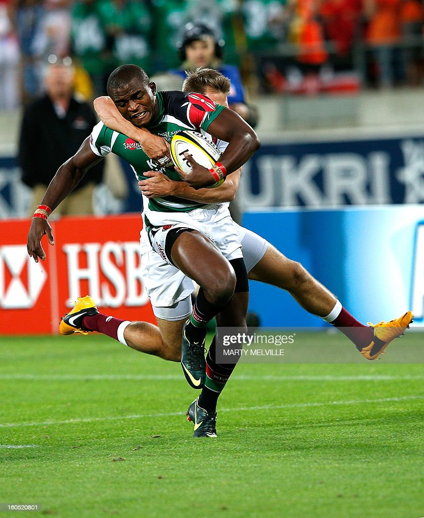 Kenya's Willy Ambaka (L) is tackled by England's Christian Lewis-Pratt during the cup final at the Westpac Stadium on day two of the fourth leg of the IRB Rugby Sevens World Series in Wellington on February 2, 2013. AFP PHOTO / Marty MELVILLE