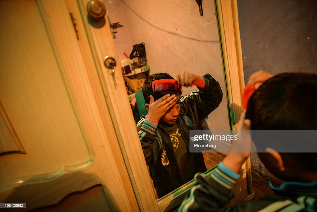 Kenyi Barja, 9-years-old, combs his hair as he gets ready for school in the town of La Oroya, Peru, on Wednesday, March 20, 2013. Most of La Oroyaís children suffer elevated lead levels, according to the Peruvian government. The question of responsibility for lead pollution in La Oroya is at the center of high-stakes clash between Peru and U.S. billionaire Ira Rennert, who owned Doe Run Peru for more than a decade through Renco Group Inc., a metals, mining and industrial conglomerate based in New York that has said it is not responsible for the childrenís ills. Photographer: Meridith Kohut/Bloomberg via Getty Images