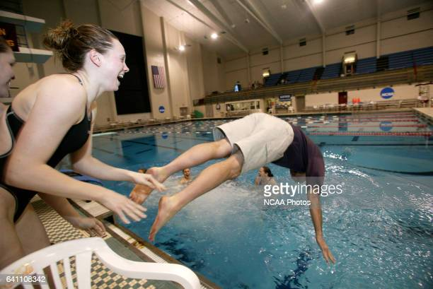 Kenyon head coach Jim Steen is thrown into the pool by Hillary Strong and teammates to celebrate Kenyon's first place finish following the Division 3...