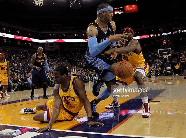 Kenyon Martin of the Denver Nuggets scrambles for a loose ball with Chris Hunter and Cartier Martin of the Golden State Warriors at Oracle Arena on...