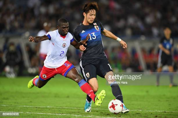 Kenyu Sugimoto of Japan and Carlens Jean Fedlaire Ruby Arcus of Haiti compete for the ball during the international friendly match between Japan and...