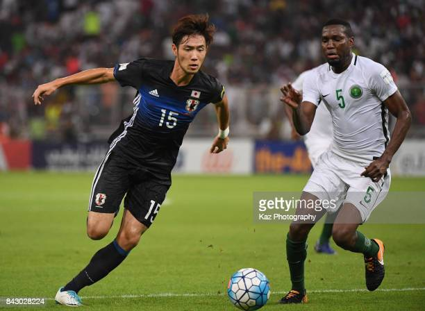 Kenyu Sugimoto of Japan and Omar Othman of Saudi Arabia compete for the ball during the FIFA World Cup qualifier match between Saudi Arabia and Japan...