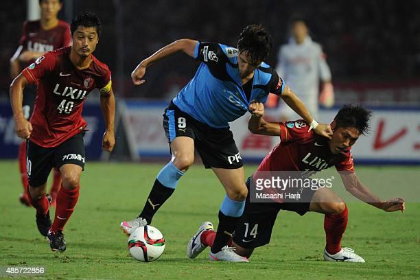 Kenyu Sugimoto of Kawasaki Frontale and Hwang Seok Ho of Kashima Antlers compete for the ball during the JLeague match between Kawasaki Frontale and...