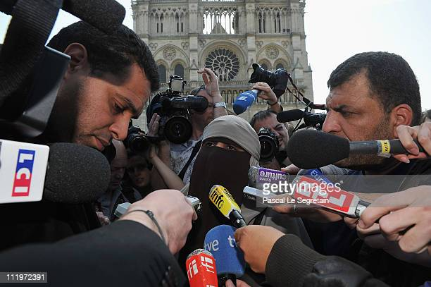 Kenza Drider addresses the media as she demonstrates against the ban of the 'niqab' or fullface veil in public places outside NotreDame cathedral on...