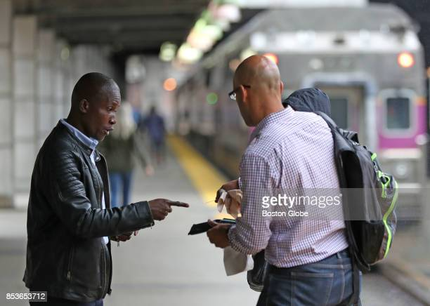 Keolis fare checker left asks a passenger to show a ticket before boarding a train on the MBTA commuter rail platform at South Station in Boston on...