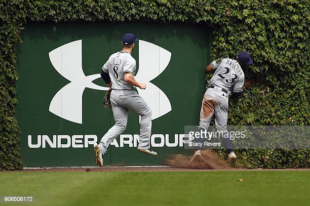Keon Broxton of the Milwaukee Brewers collides with the left field wall during the third inning of a game against the Chicago Cubs at Wrigley Field...