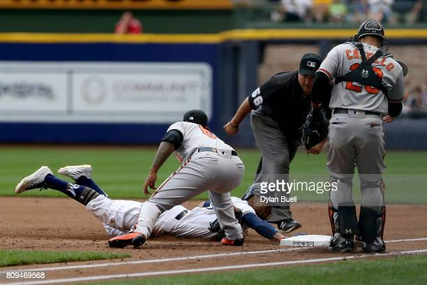 Keon Broxton of the Milwaukee Brewers dives into first base past the tag attempt of Jayson Aquino of the Baltimore Orioles during a run down in the...
