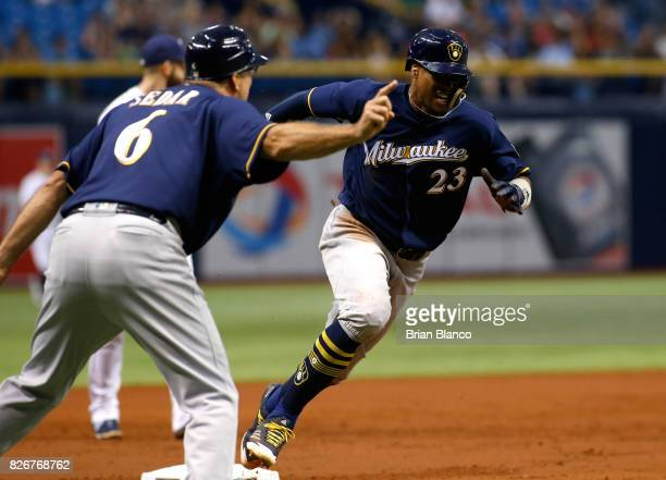 Keon Broxton of the Milwaukee Brewers rounds third base as third base coach Ed Sedar signals him home to score off of an RBI double by Orlando Arcia...
