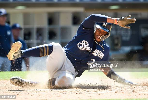 Keon Broxton of the Milwaukee Brewers slides as he scores during the ninth inning of a baseball game against the San Diego Padres at PETCO Park on...