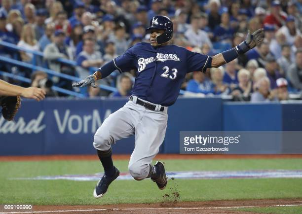 Keon Broxton of the Milwaukee Brewers slides home safely to score a run in the third inning during MLB game action against the Toronto Blue Jays at...